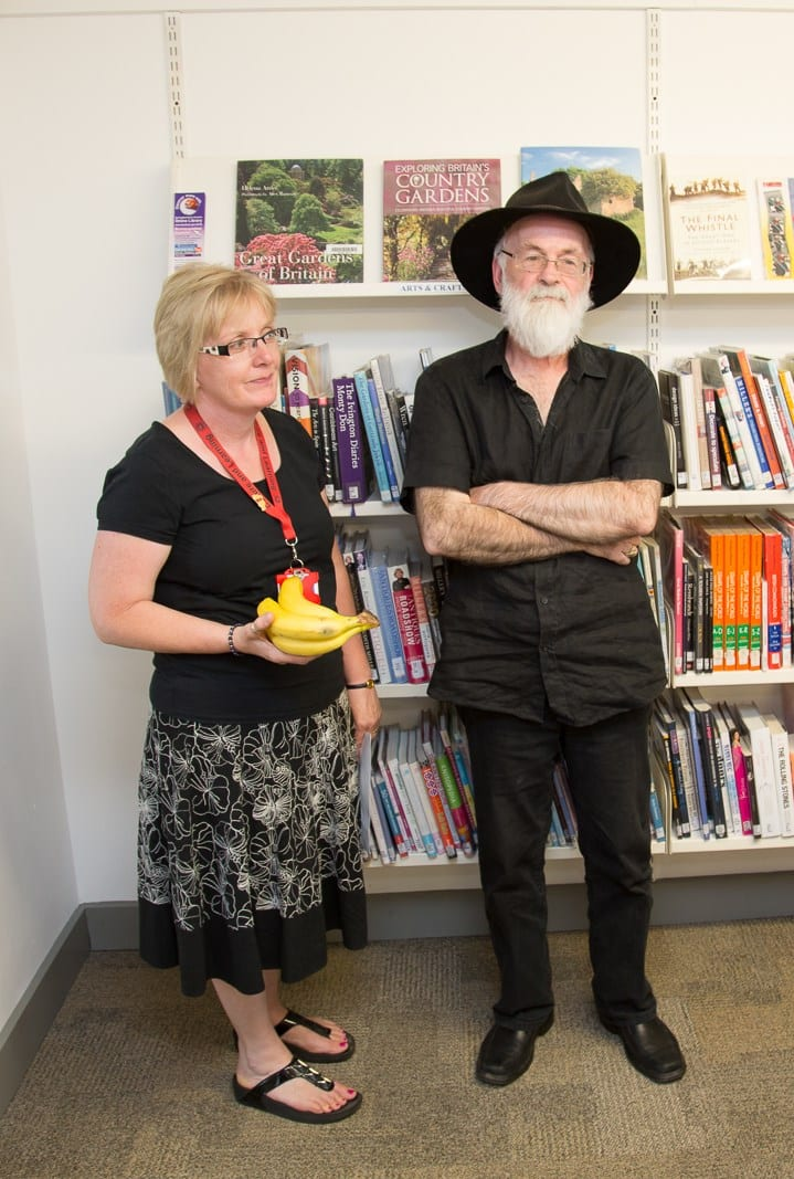 Sir Terry with Beaconsfield Library's customer service assistant Carolin Ing during his visit in July 2013. Carolin is holding a banana as The Librarian in Discworld is an orang-utan