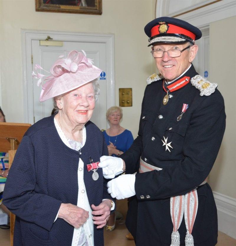 Joyce Brooker receives her medal from Sir Henry Aubrey-Fletcher