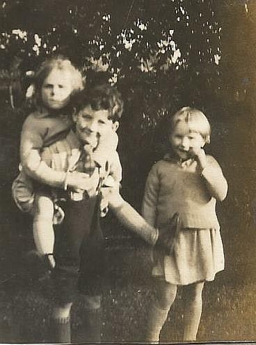 Ron Philbey, son of Arthur Philbey, carrying small girl. Jean Orme, her sister, aged 4, is standing.