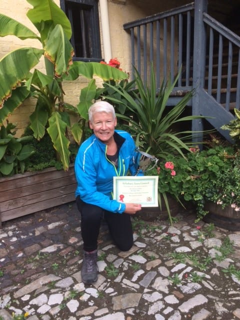 Sara Shelby with the plaque and trophy in the garden at the King's Head