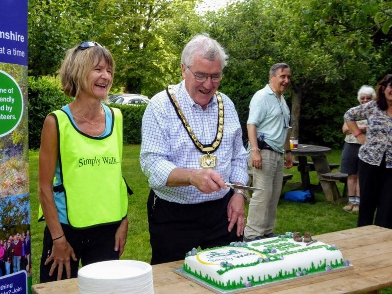Chairman Brian Roberts and Simply Walk Officer Fiona Broadbent cut the cake