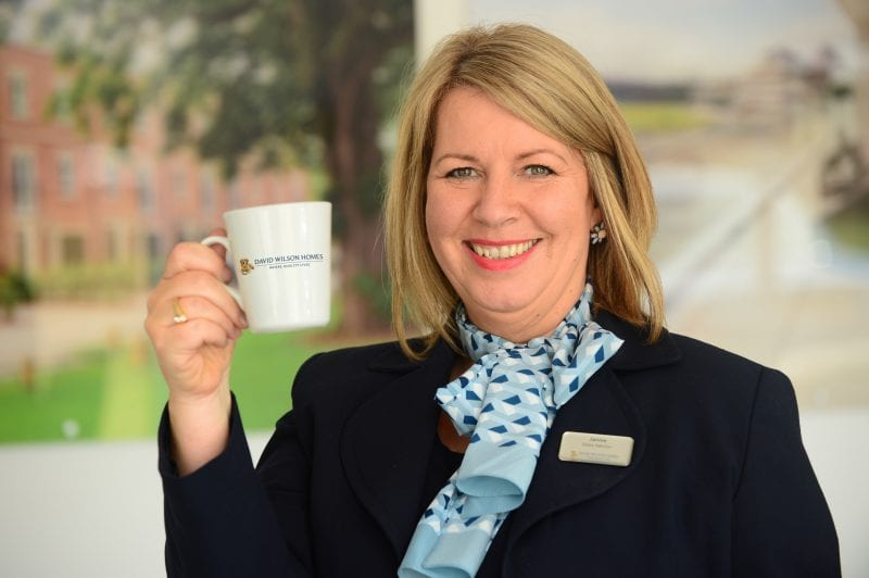 A Sales Adviser holding a mug for Macmillan Coffee Morning.