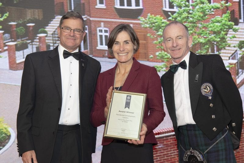 Andrea Fawell, Sales Director of Kebbell accepts award from Stuart Shield - President of the International Property Awards (left) and Peter Bolton-King - Director at RICS Global Standard
