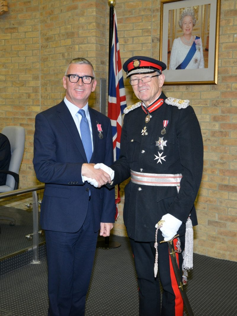 Sean Wheeler receives his British Empire Medal from Sir Henry