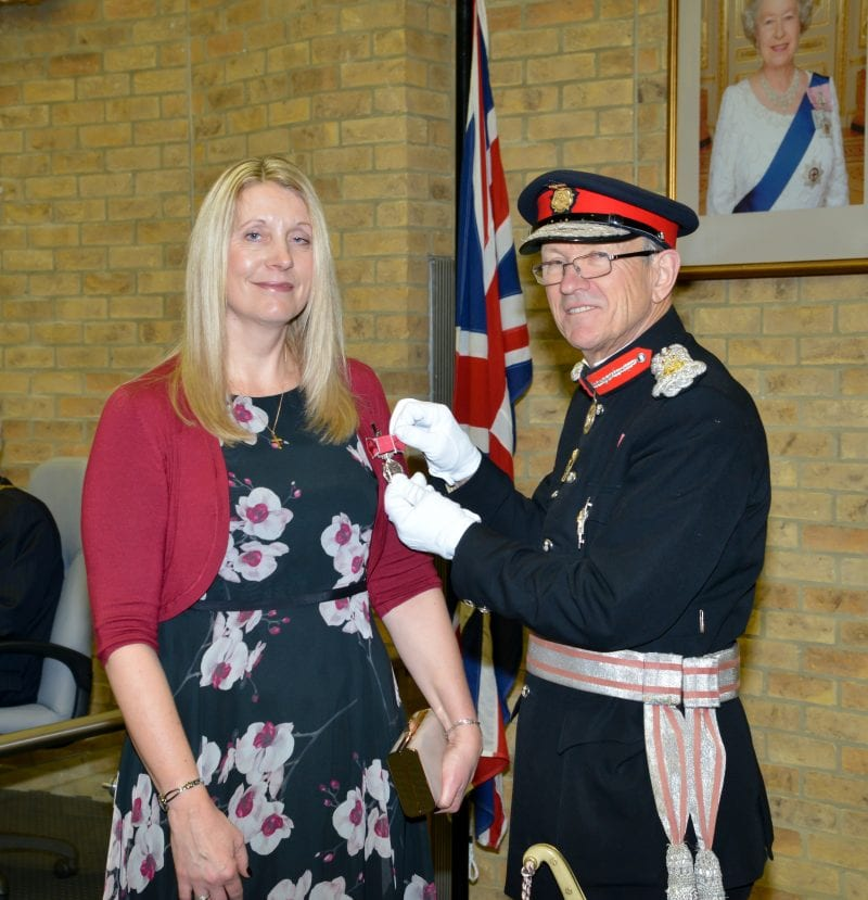 Trudie Bird receives her British Empire Medal from Sir Henry